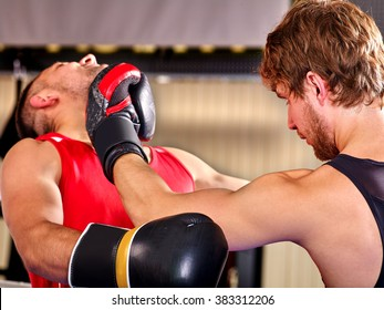 Two  men boxer wearing helmet and  gloves boxing .They beat each other in jaw.