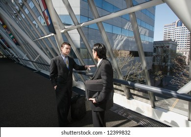 Two men in business suits chatting in an urban walkway on a sunny day