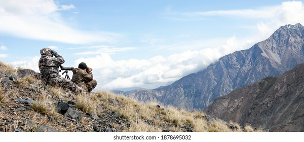 Two men in camouflage conduct surveillance high in the mountains. Hunters use optics to search for hunting objects on the mountainside.