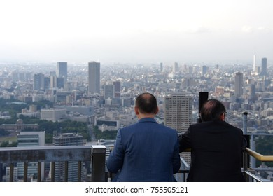 Two men CEO business meeting on the rooftop of roppongi with Tokyo cityscape viewings