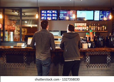 Two men choose food in a fast food restaurant.