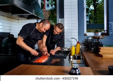 Two men cook chef cut up, cooked fish in restaurant commercial kitchen.