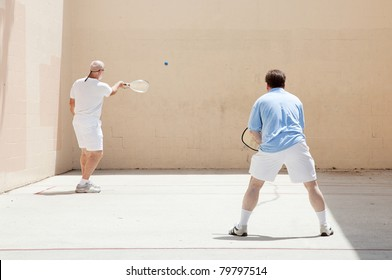 Two men, could be father and son, playing racquetball together.