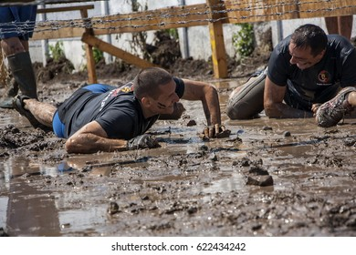 Two men crawling under barbed wire and having fun during strength race Legion Run held in Sofia, Bulgaria on 26 July 2014