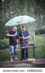 Two men (dad and son) are saving shashlik from rain with sun umbrella. Image with selective focus and toning