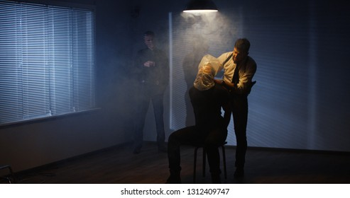 Two men in dark room examining caught men in handcuffs tormenting and hurting him with plastic bag while asking about drugs
