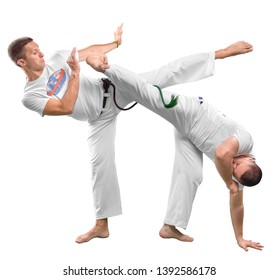 Two men do the fighting element of capoeira. A couple of fighters train capoeira isolated on white background - concept about people, lifestyle and sport.