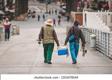Two men dressed for fishing and with their fishing poles, walk with a blue cooler filled with fish after fishing on the pier in the Pacific Ocean.