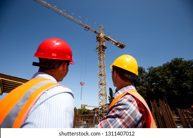Two men dressed in orange work vests and  helmets look at th crane on the building site