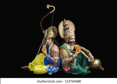 Two men dressed-up as Rama and Ravana with drinking orange juice