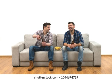 The two men drink a beer with chips on the sofa on a white wall background