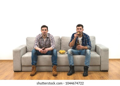 The two men drink a beer on the sofa on a white wall background