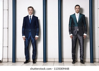 Two men in elegant suit on a wall background