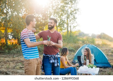 Two men enjoying beer and making barbecue together