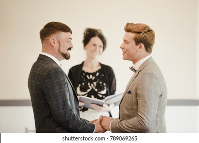 Two men are exchanging vows on their wedding day.