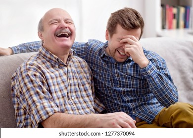 Two men father and son are sitting on the sofa in the living room at home and remember the funny events from the past. They laugh at the joke. Good family relationships