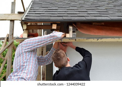 Two men father and teen son installing wooden plank frame for eaves of gray asphalt shingles roof back view. Home improvement and diy concept.