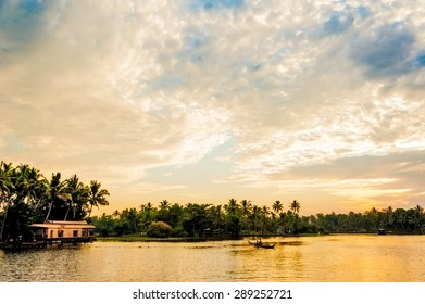 Two men fishing in the Kerala backwaters near Alappuzha at sunset.