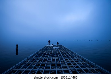 Two men fishing on the pier. Foggy seascape. Blue sea in a foggy morning.