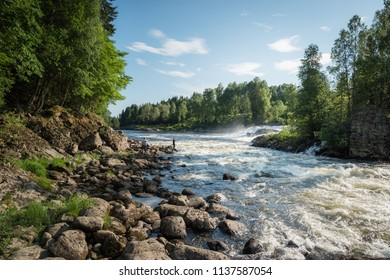 Two men fishing salmon in a river in Norway