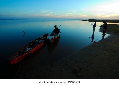 Two men fishing seaside  in the early morning.