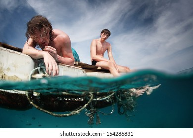 Two men floating in a sea with sad faces