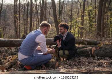 two men, gay couple, cuddling with dog puppy. Outdoors in woods, leisure time.