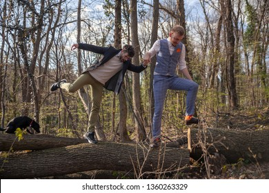 two men, gay couple holding hands, walking in woods, helping each other cross a log.