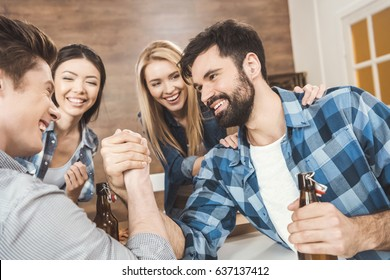 Two men with hands clasped in arm wrestling challenge while women on background looking at them