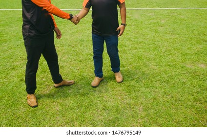 Two men handshaking to each other standing on a ground