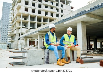 Two men in helmets and waistcoats having nice conversation and holding cups of hot drinks while sitting on cement beam during break on construction site
