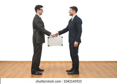 The two men hold a metal case on the white wall background