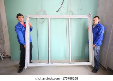 Two men holding new window frame in a room under renovation
