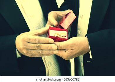 Two men Holding Wedding Rings