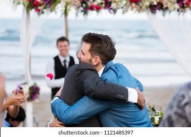 Two men hugging at wedding ceremony