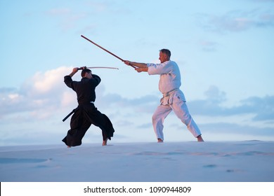 Two men, in Japanese clothes, are practicing martial arts with a traditional Japanese weapon - a katana and jo, attack each other in the desert during sunset on the background of blue sky.