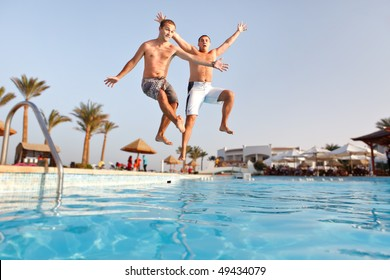 Two men jumping in swimming pool together.  Low angle view from the swimming pool.