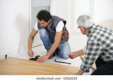 Two men laying parquet