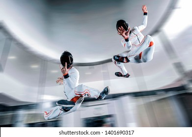 Two Men levitation in yoga asana. Freedom in free fly. Indoor skydiving flying.