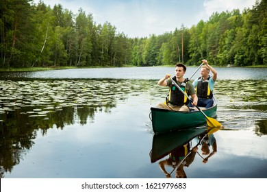 Two men in life vests canoeing in forest lake. Water surface covered with water lilies. Tourists traveling in Finland, having adventure.