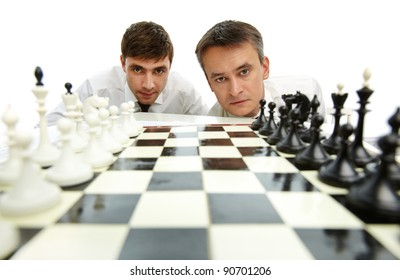 Two men looking at camera with chess figures on chess board in front