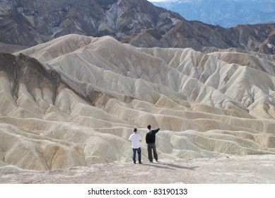 Two men looking at an expansive mountain scene in Death Valley, California, USA