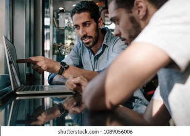 Two men looking at laptop computer and discussing ideas and designs at a sports shop. Man pointing at the screen and explaining ideas.