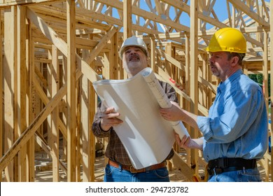 Two men looking at plans on construction site