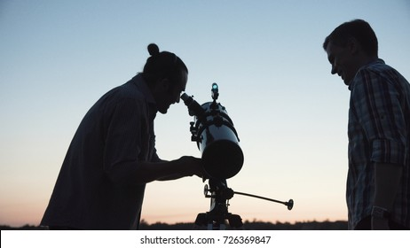 Two men looking through telescope discovering stars in twilight.
