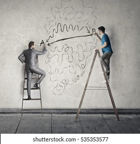 Two men making art on the wall while on a ladder