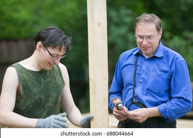 Two men measuring the level while building house outside