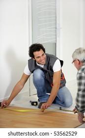 Two men measuring parquet