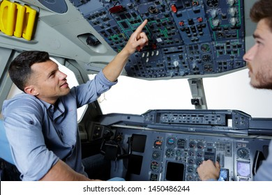 two men in modern flight simulator for pilot training