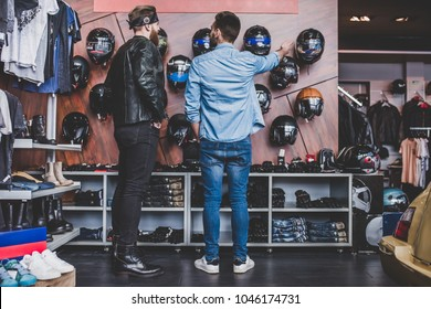 Two men in motorcycle shop. Customer and salesman. Shop assistant is helping bearded man in choosing new vehicle, motorcycle accessories and other biker stuff. Buying new helmet.Safety driving concept